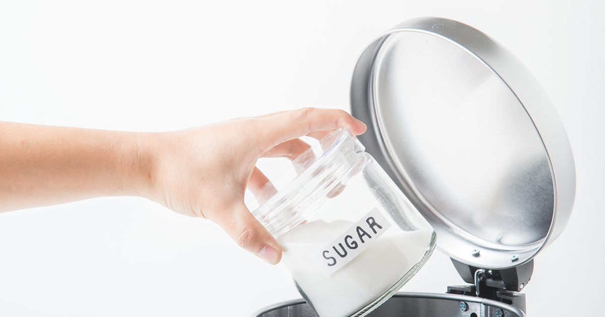 a jar of sugar being tossed in the trash