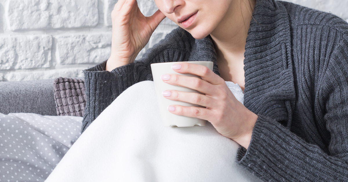 A woman with the flu covered with a blanket and drinking hot tea