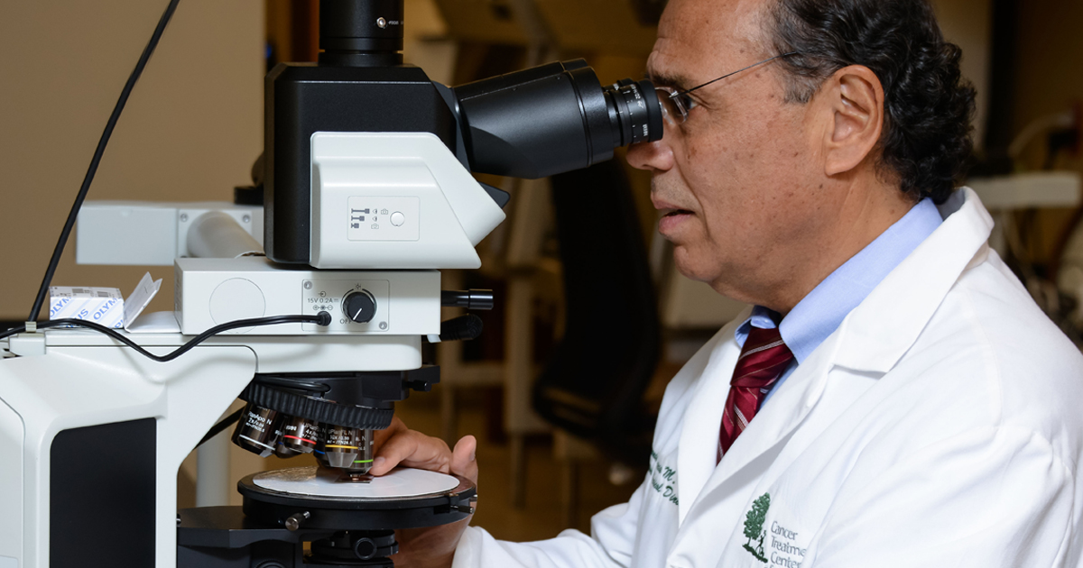 Pathologist reviewing a specimen under the the microscope