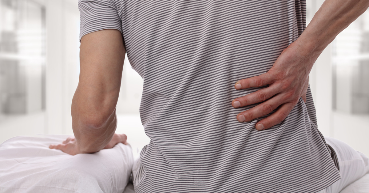 a male patient experiencing back pain with his hand on his back