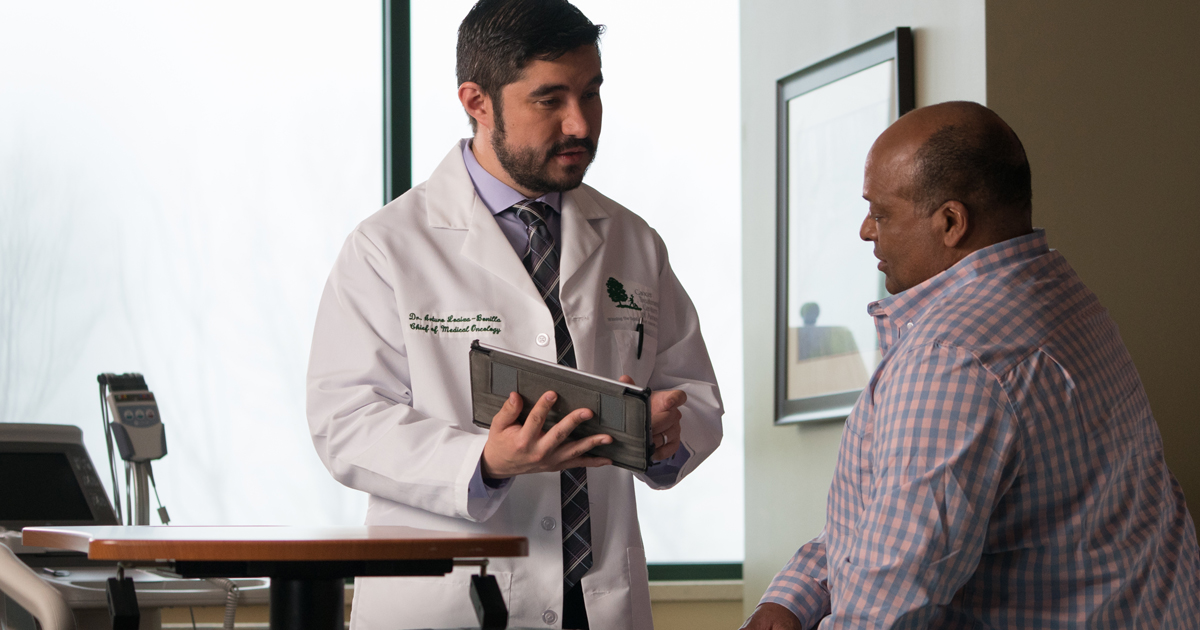A male physician discussing paperwork with a male physician