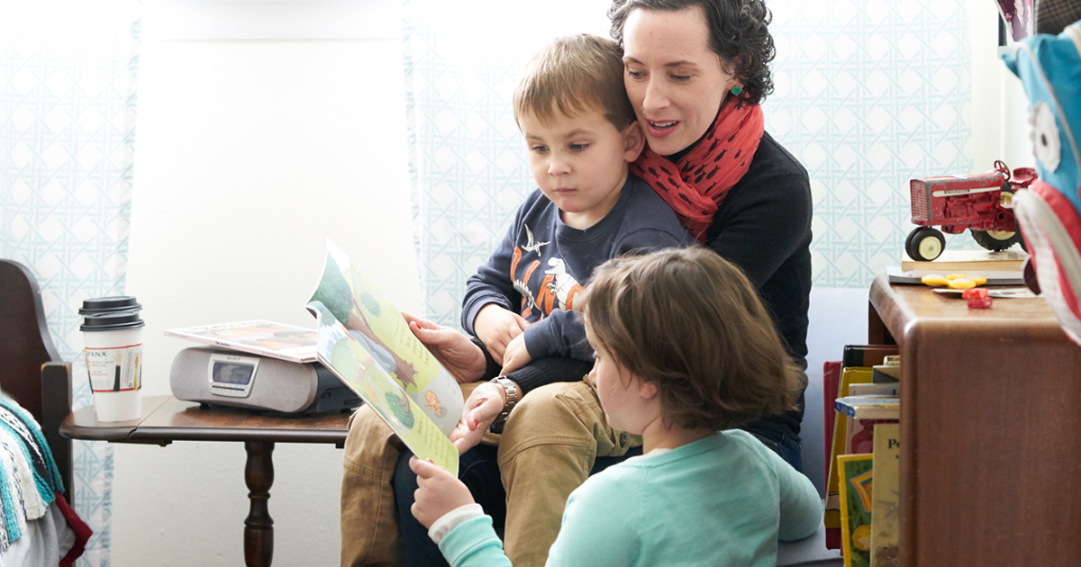 A mother reading a book about cancer with her children