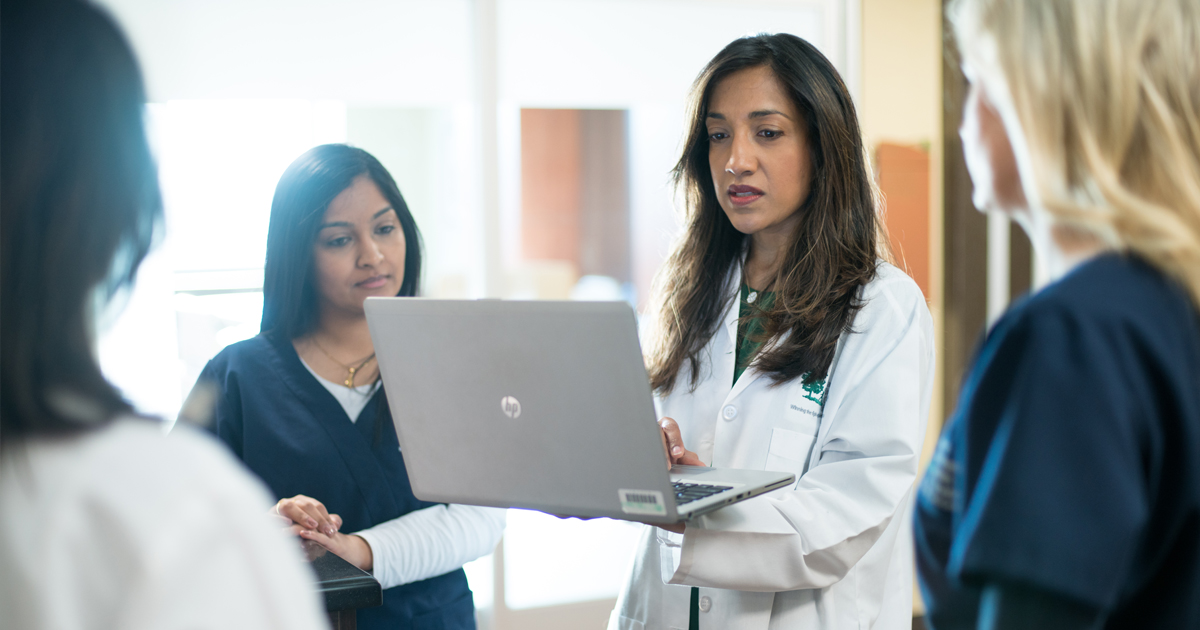 A female oncologist in a white lab coat sharing information from a laptop with female clinicians in scrubs