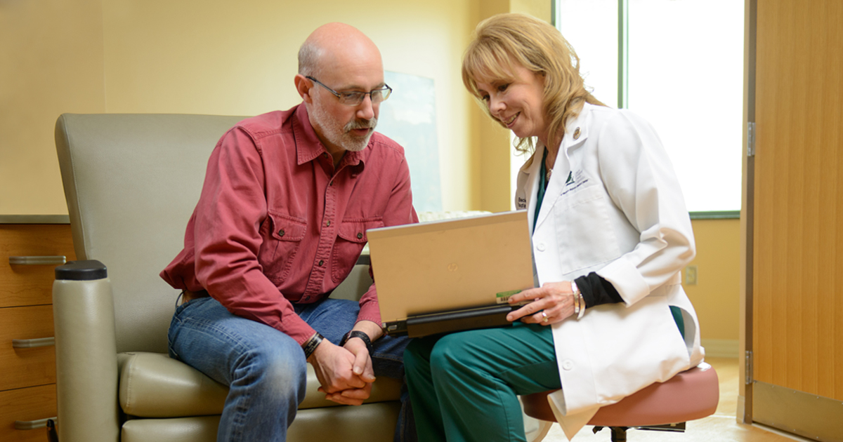 A female physician holding a laptop and clarifying questions and concerns about cancer with a patient