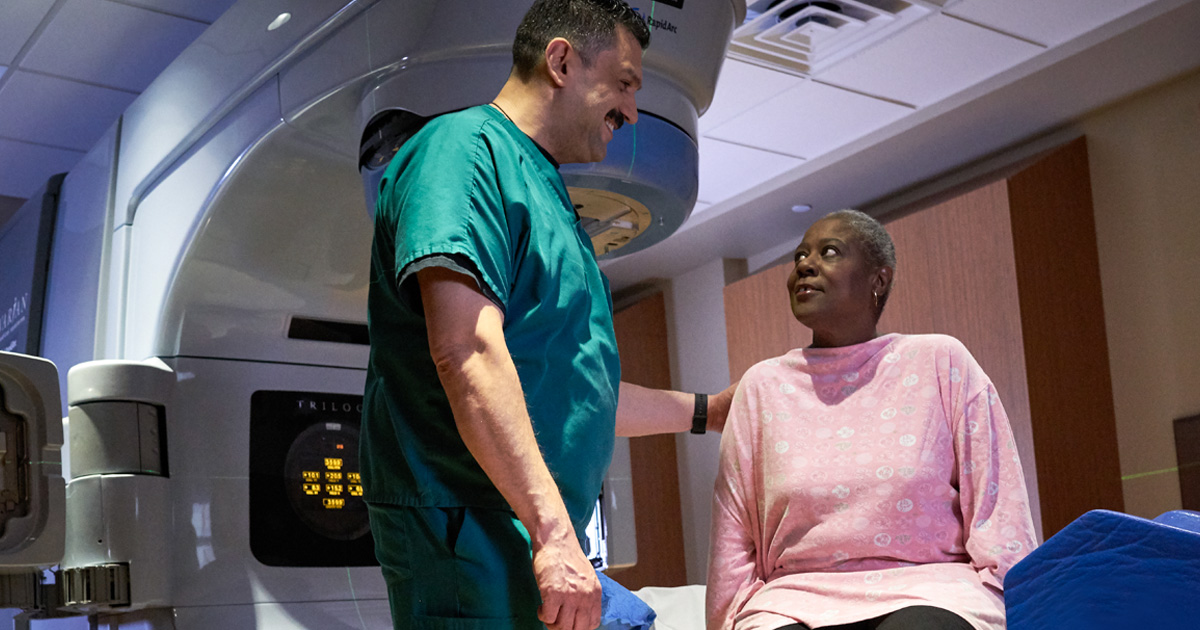 A male doctor in scrubs assisting a female patient undergoing radiation