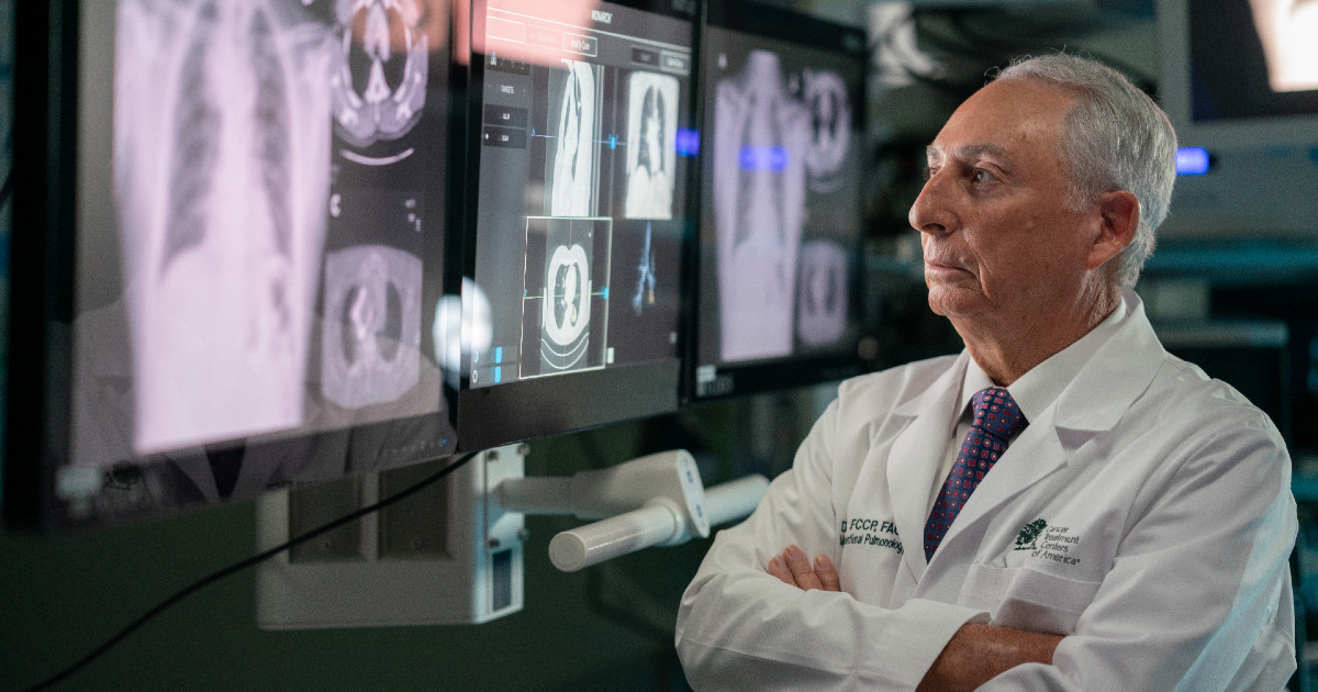 doctor crosses his arms while looking at lung x ray diagrams