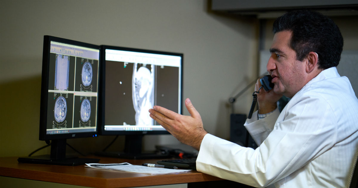 doctor looking at x ray diagram while discussing on the phone