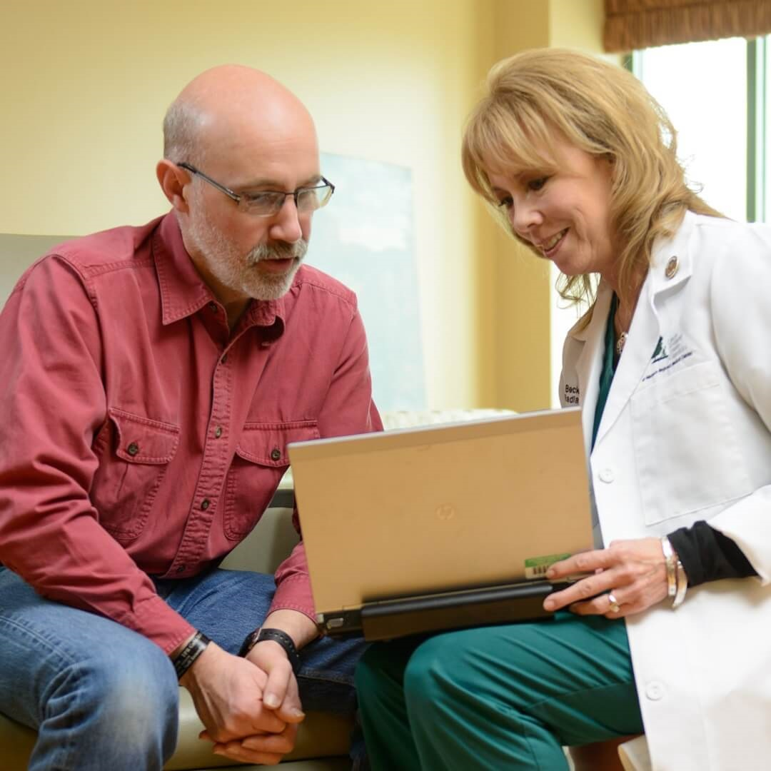 male patient reviewing treatment options with doctor over laptop