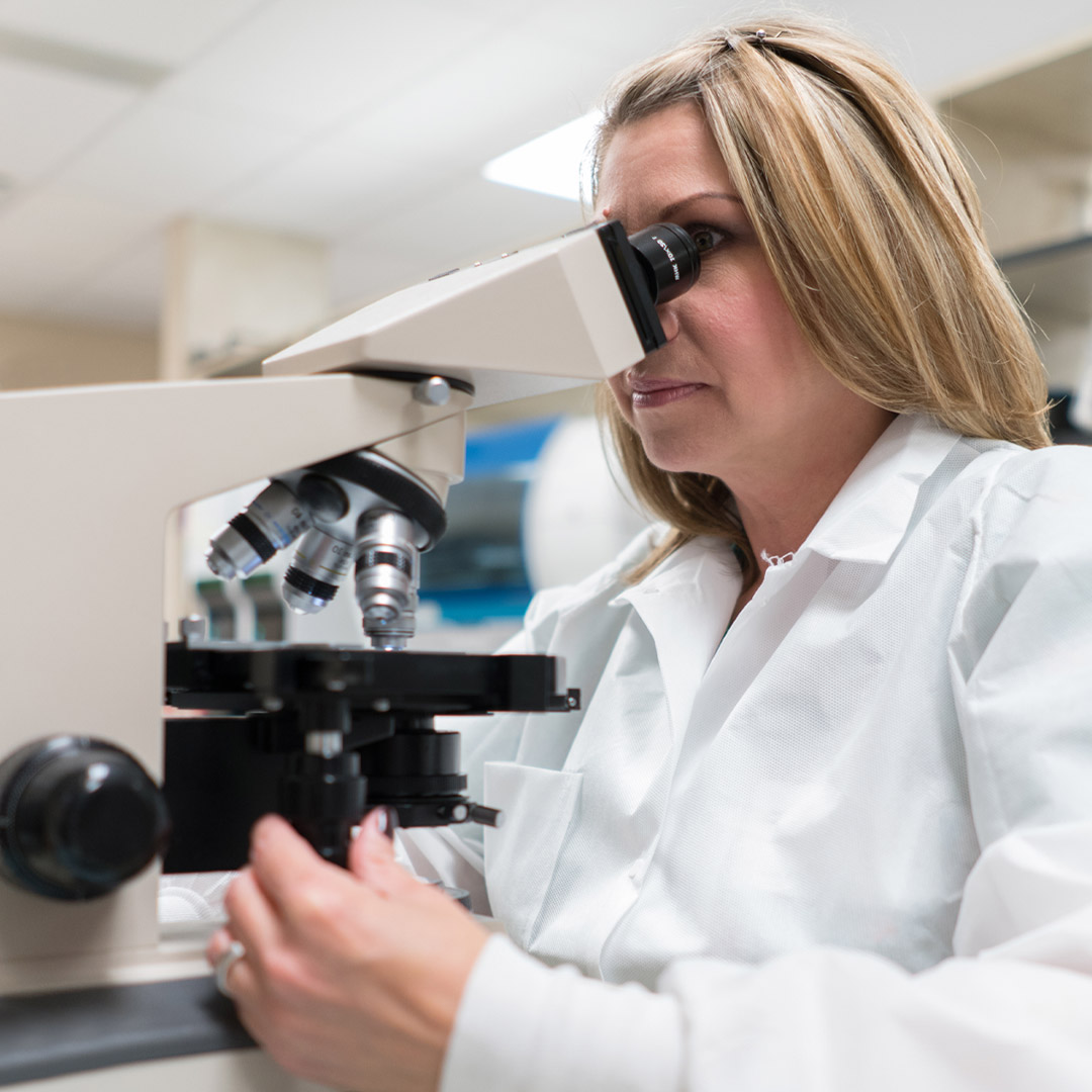 female scientist viewing cancer through a microscope