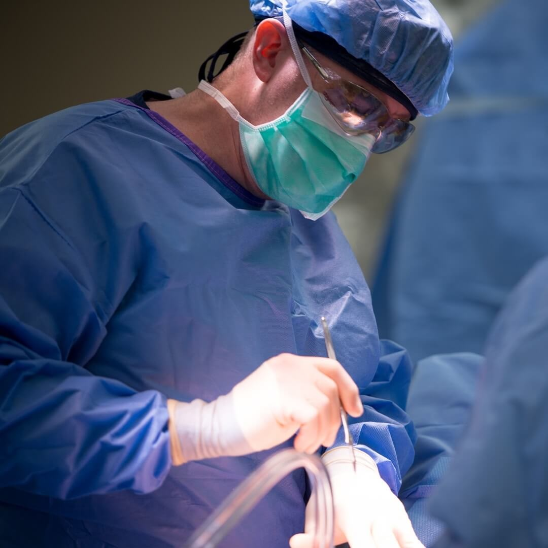 close-up of surgeon with mask and scrubs performing surgery task