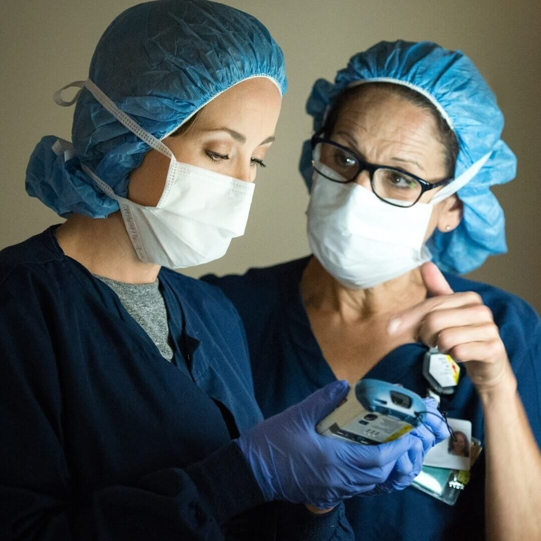 male and female doctor in smocks using endoscope to inspect lungs for cancer