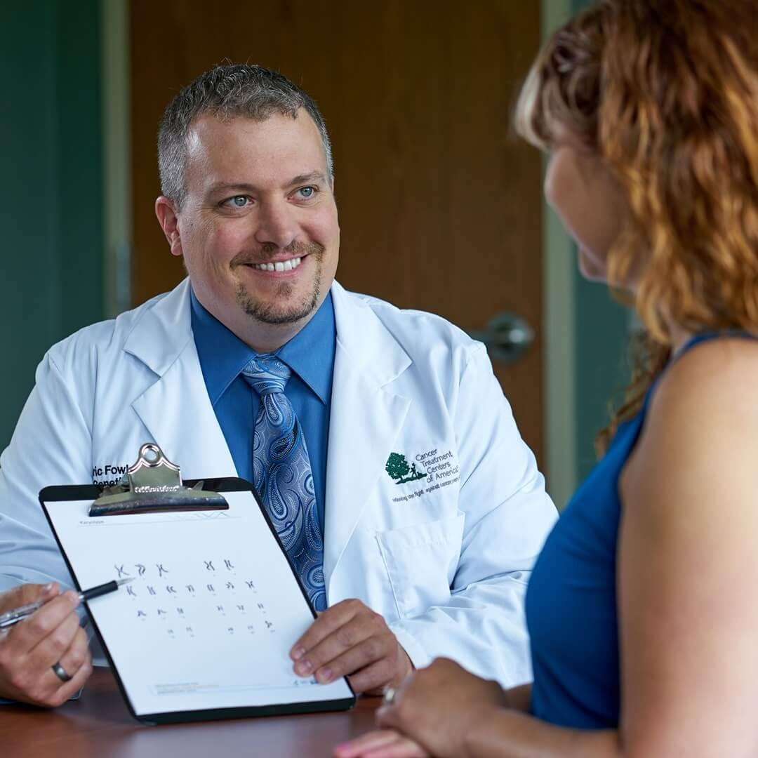male doctor in white coat reviewing clipboard of treatment options with female patient